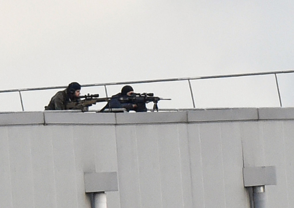 TOPSHOTS Police marksmen take up a position on a roof in Dammartin-en-Goele, north-east of Paris, where two brothers suspected of slaughtering 12 people in an Islamist attack on French satirical newspaper Charlie Hebdo held one person hostage as police cornered the gunmen, on January 9, 2015. The hostage drama unfolded at a printing business in the small town of Dammartin-en-Goele, only 12 kilometres (seven miles) from Paris's main Charles de Gaulle airport, police sources said. AFP PHOTO / DOMINIQUE FAGET